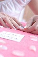 woman putting false fingernails