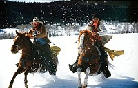 Two cowboys riding horses in a snow covered landscape