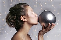 young woman kissing christmas ornament