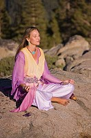 Mature woman in flowing robes meditating on a rock