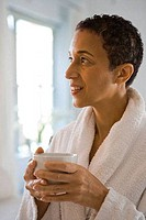 Close_up of a mature woman holding a cup of coffee and smiling