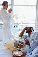 Mid adult man lying on the bed and listening to music with a mature woman standing beside him