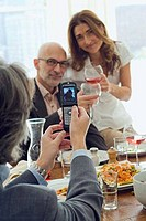 Rear view of a man taking a picture of a couple toasting with wine glasses