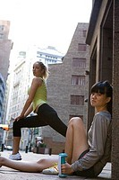 Side profile of a young woman relaxing with another young woman stretching her legs