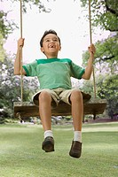 Mixed race boy swinging in backyard
