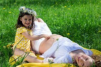 Pregnant woman and daughter relaxing in park