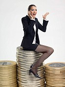 Businesswoman sitting on stack of coins