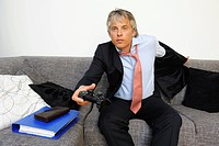 Portrait of businessman playing video games, studio shot