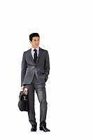 Businessman with briefcase and newspaper listening to MP3 player, cut out (thumbnail)