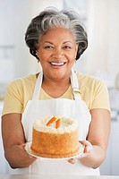 African woman holding out fresh carrot cake