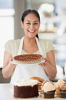 Hispanic woman holding pie in bakery