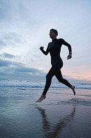 Hispanic woman in wetsuit running on beach