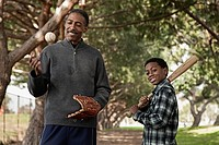 African man and son with baseball bat and glove in park