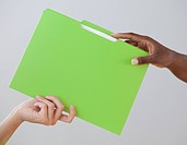 African woman handing co_worker a folder
