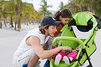Hispanic father and daughter checking on baby in stroller