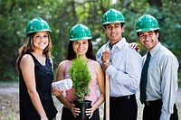 Hispanic business people planting trees in forest