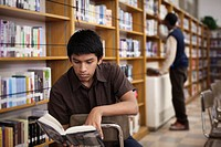 Hispanic teenage boy reading in school library
