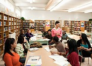 Teacher talking to students in school library