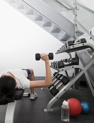 Hispanic woman using hand weights in health club