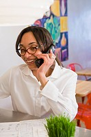 Mixed race woman talking on telephone in cafe
