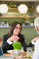 Mixed race businesswoman having lunch with co_worker