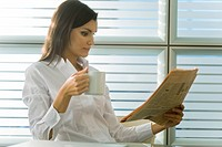 Professional woman reading newspaper and drinking coffee