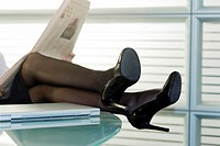 Professional woman reading newspaper with legs up on desk (thumbnail)