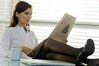 Professional woman reading newspaper with legs up on desk