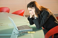 Businesswoman looking at laptop holding her head