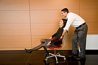 Office worker pushing coworker in office chair