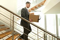 Businessman on office staircase with box of belongings (thumbnail)