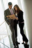 Businessman and businesswoman looking at financial newspaper