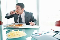 Businessman eating pizza with French fries at desk