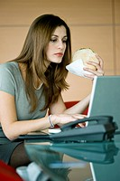 Businesswoman eating pita sandwich at laptop
