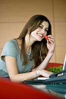 Businesswoman eating a strawberry at laptop