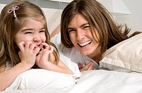 Young woman and girl on bed smiling