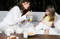 Young woman and girl having breakfast outdoors