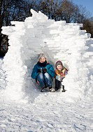 Girl and boy in igloo in the snow