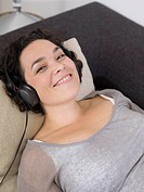 woman smiling, headphones on.
