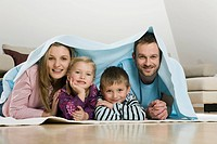 Family covered with blanket, smiling
