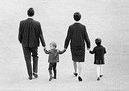 Sixties, black and white photo, people, young family takes a walk, all go hand in hand, man, aged 25 to 35 years, woman, aged 25 to 35 years, boy, age...