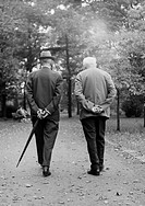 Sixties, black and white photo, people, seniors, two older men walk through the park, walking stick, suit, hat, aged 70 to 80 years
