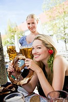 Germany, Bavaria, Upper Bavaria, Young woman in beer garden holding pretzel, portrait