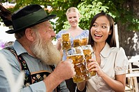 Germany, Bavaria, Upper Bavaria, Bavarian man and Asian woman in beer garden raising stein glasses, portrait