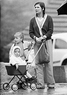 Seventies, black and white photo, people, mother and two children with a baby carriage wait in the rain, woman, aged 30 to 35 years, boy, aged 3 to 4 ...