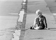 Seventies, black and white photo, people, children, little boy sits on a pavement and plays with a stick in a puddle, aged 3 to 5 years