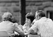 Seventies, black and white photo, people, bored young girl and her parents sit in a beer garden nibbling ice cream, father drinks a beer, girl, aged 1...
