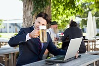 Germany, Bavaria, Upper Bavaria, Young business man in beer garden holding beer stein, portrait