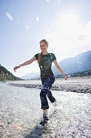 Germany, Bavaria, Tölzer Land, Young woman running through river, smiling