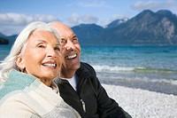 Germany, Bavaria, Walchensee, Senior couple relaxing on lakeshore